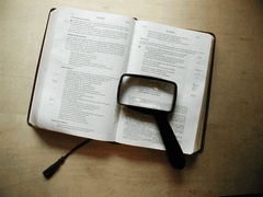 image of Bible and magnifying glass