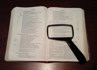 picture of open bible and magnifying glass