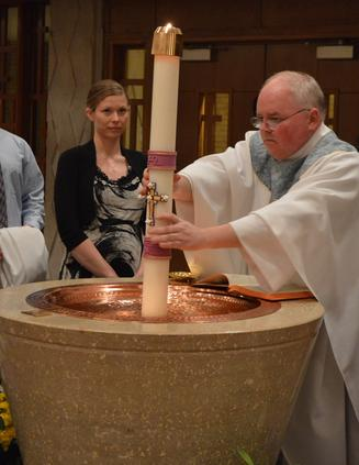Priest plunges paschal candle into baptismal font at Easter Vigil