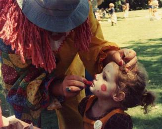 photo of clown applying clown makeup to child's face